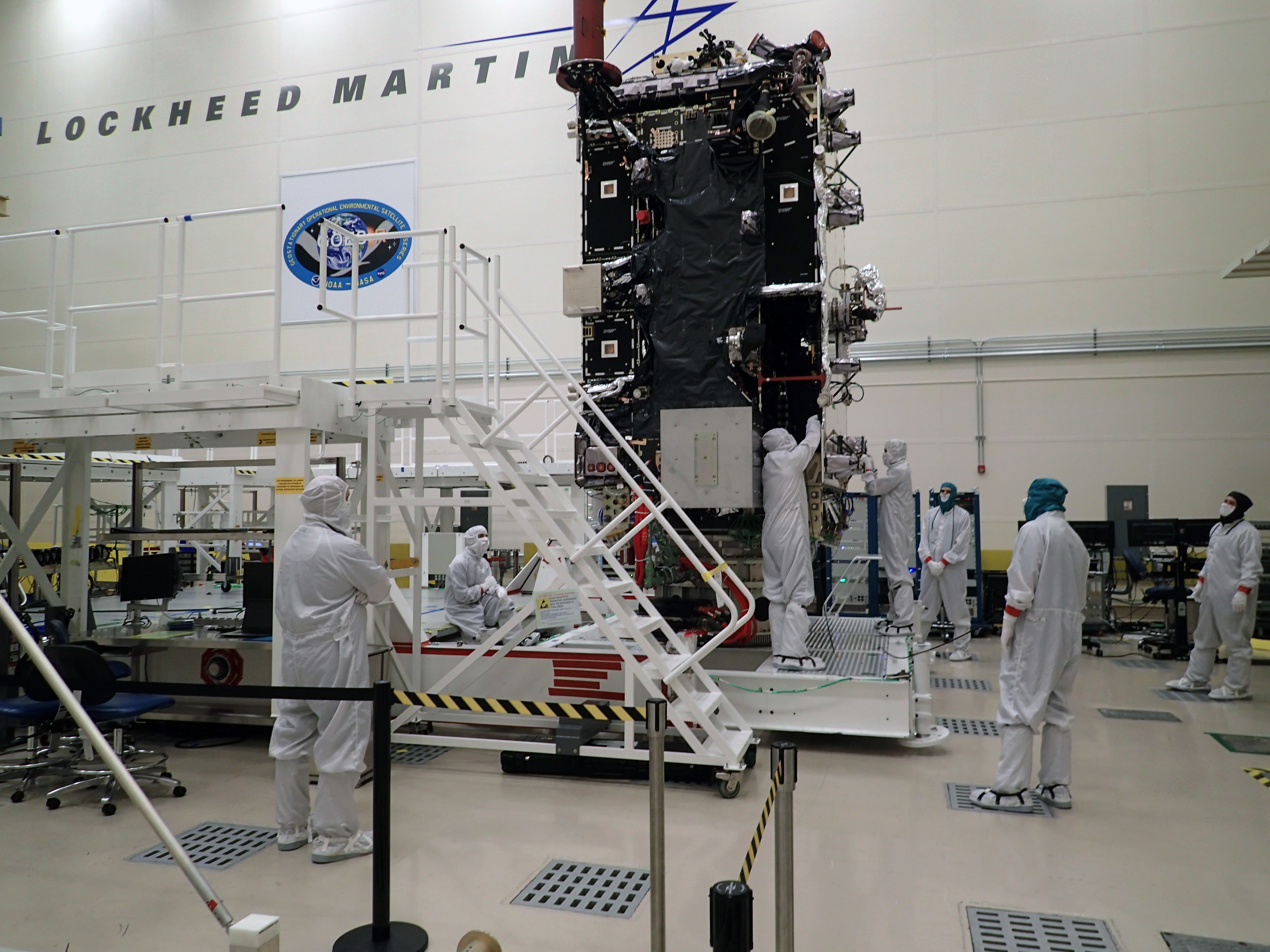 Technicians work on GOES-T in a clean room