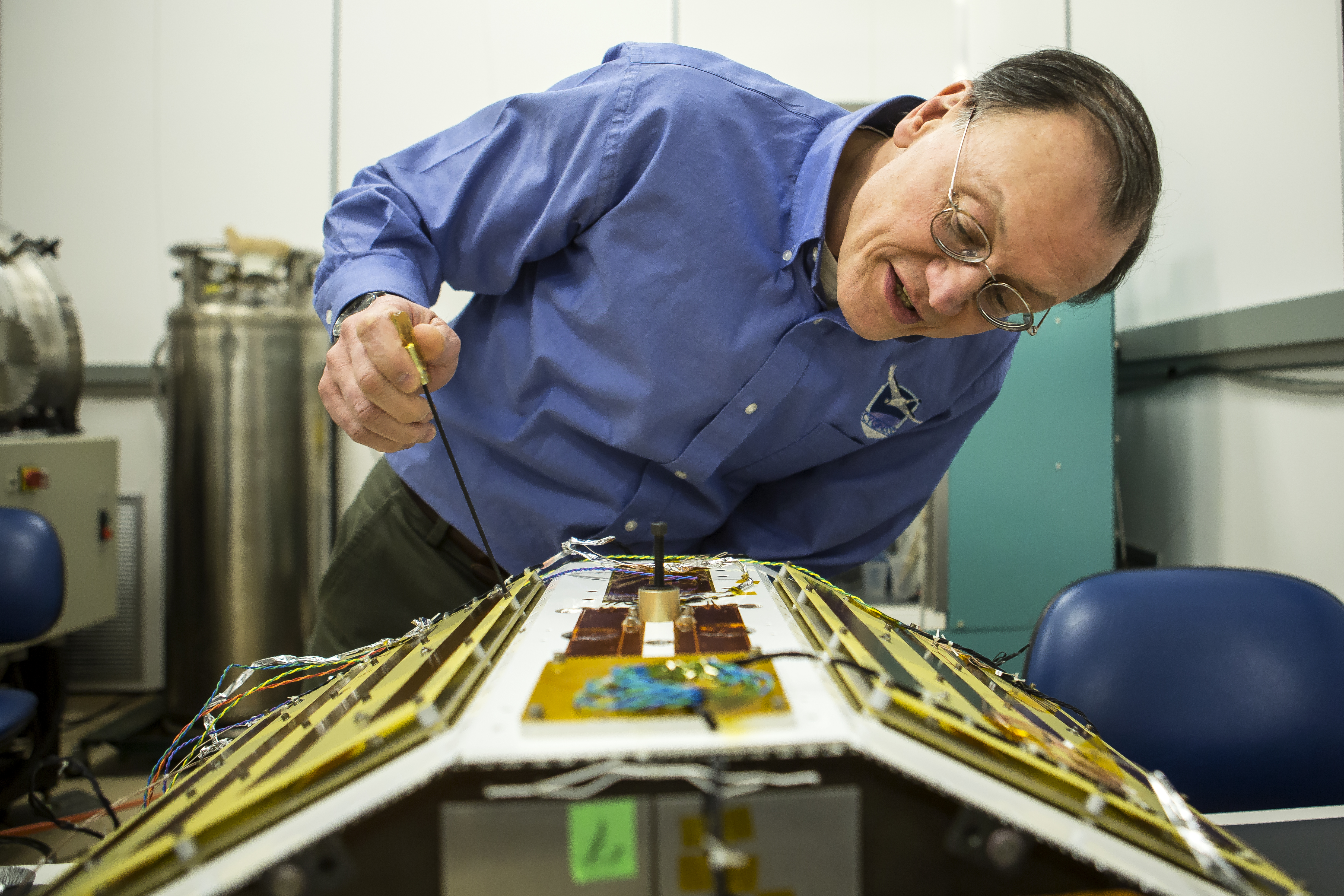 Christopher Ruf, Director of the Space Physics Research Laboratory and Atmospheric, Oceanic and Space Sciences Professor at the University of Michigan, inspects CYGNSS, February 12, 2015.