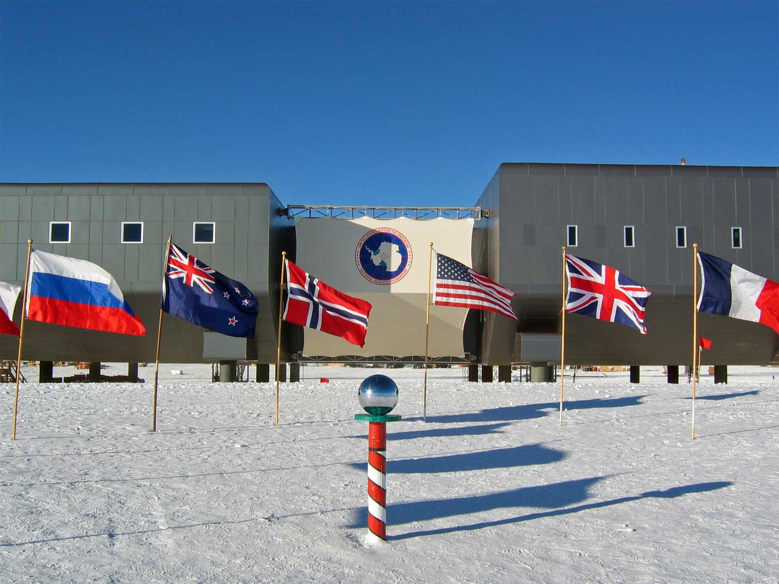 The Amundsen–Scott South Pole Station during the 2007–08 summer season.  In the foreground is the ceremonial South Pole and the flags for the original 12 signatory nations to Antarctic Treaty. Credit: NSF