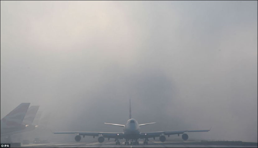 Planes on ground at airport in thick fog